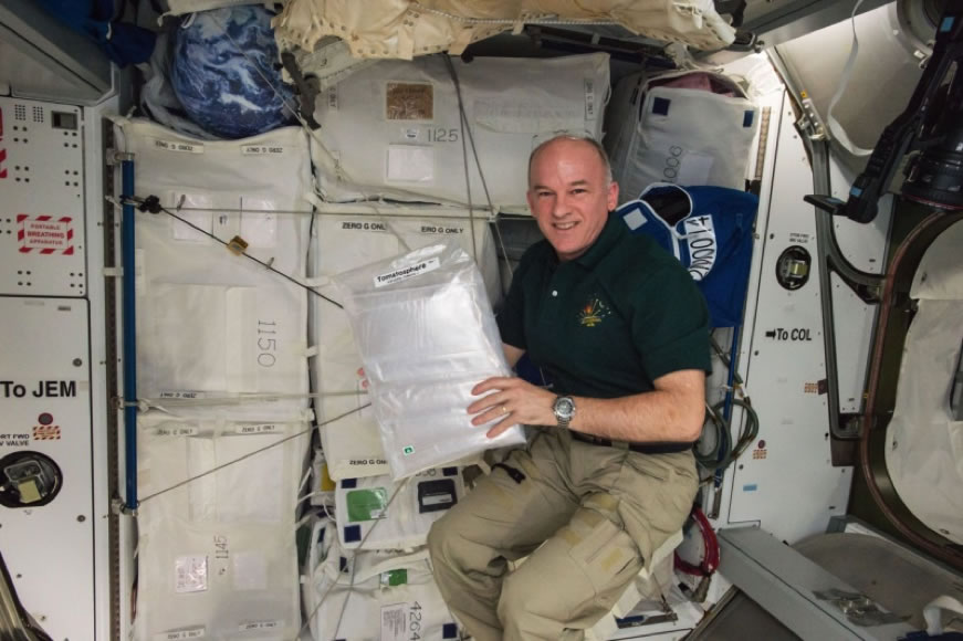 NASA Astronaut Jeff Williams floating in the International Space Station with 1.2 million Tomatosphere™ seeds
